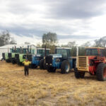 Danny stands beside farming equipment - a collection of tractors, some working and some not!
