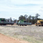 Harvesters wait neat the Farm's machinery shed